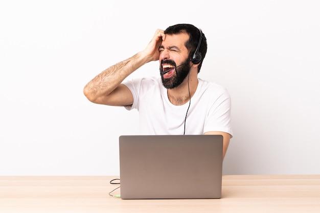 Uomo caucasico telemarketer che lavora con una cuffia avricolare e con il computer portatile ha sottolineato sopraffatto.