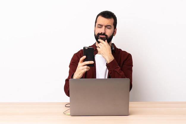 Uomo caucasico telemarketer che lavora con un auricolare e con il laptop pensando e inviando un messaggio.