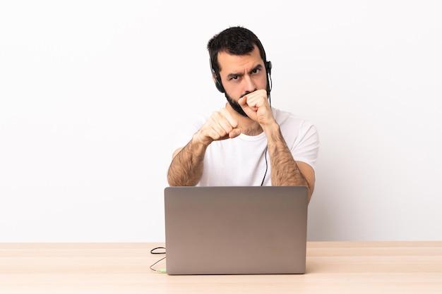 Uomo caucasico telemarketer che lavora con un auricolare e con il computer portatile con gesto di combattimento.
