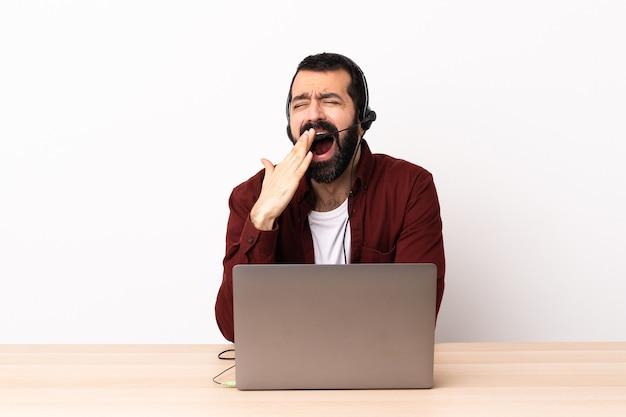 Uomo caucasico telemarketer che lavora con un auricolare e con il computer portatile che sbadiglia e che copre la bocca spalancata con la mano.