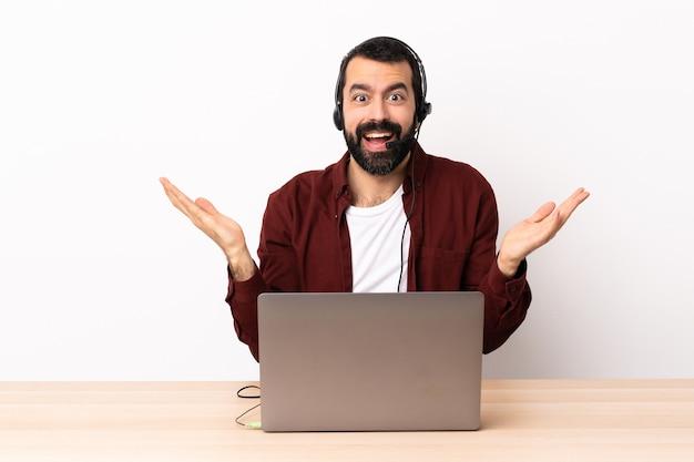 Uomo caucasico telemarketer che lavora con un auricolare e con il computer portatile