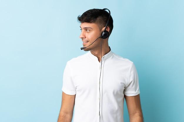 Operatore di telemarketer colombiano uomo che lavora con una cuffia sul lato dall'aspetto isolato
