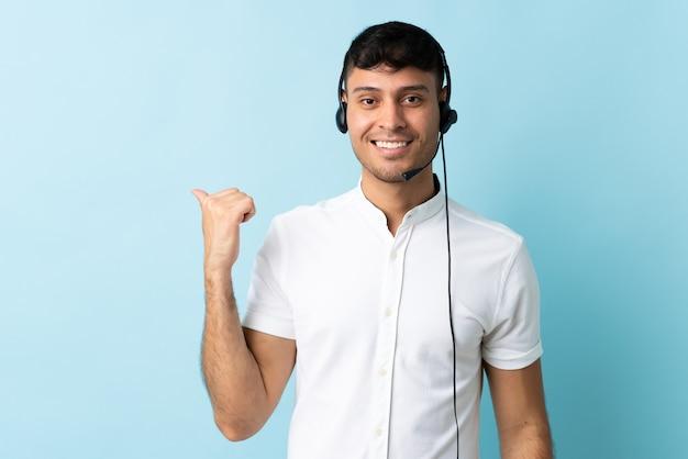 Operatore di telemarketer colombiano uomo che lavora con un auricolare sopra isolato che punta al lato per presentare un prodotto