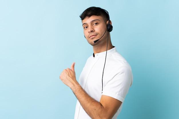 Operatore di telemarketer colombiano uomo che lavora con un auricolare isolato orgoglioso e soddisfatto di sé