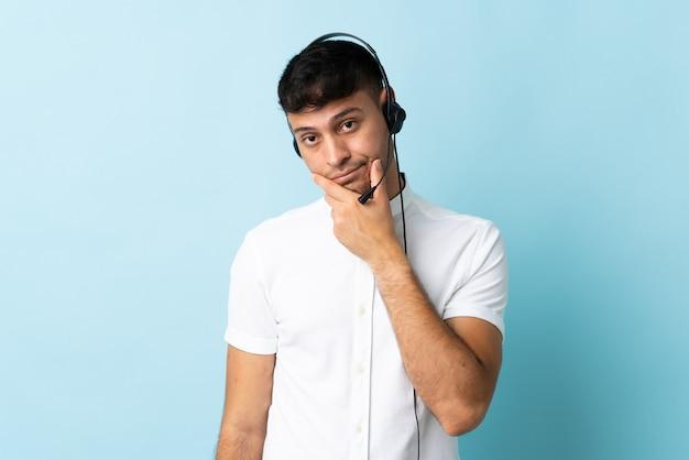 Operatore di telemarketer colombiano uomo che lavora con una cuffia sul pensiero isolato
