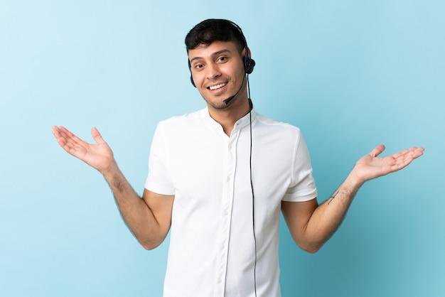 Operatore di telemarketer colombiano uomo che lavora con un auricolare sopra isolato con espressione facciale scioccata