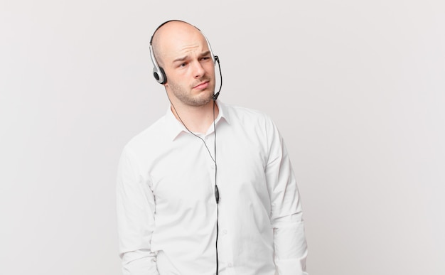 Telemarketer si sente triste turbato o arrabbiato e guarda di lato con un atteggiamento negativo accigliato in disaccordo