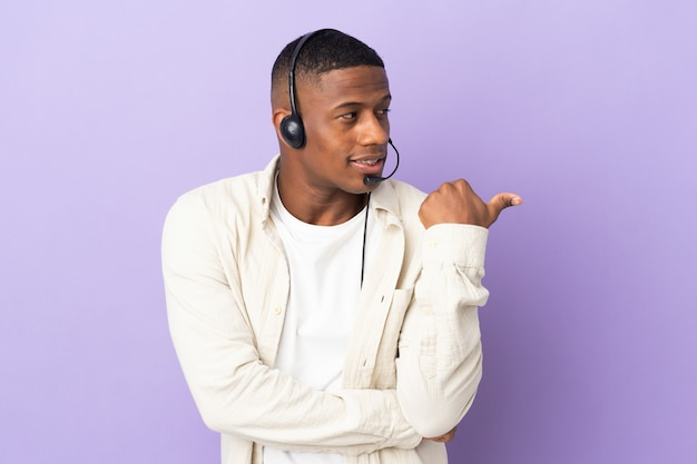 Operatore di telemarketer latino uomo che lavora con un auricolare isolato su viola che punta di lato per presentare un prodotto