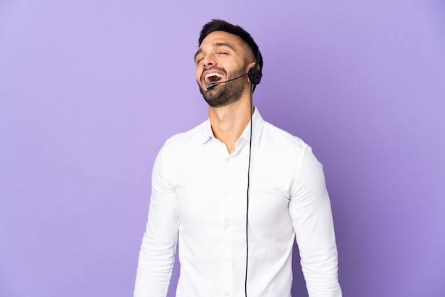 Telemarketer uomo che lavora con un auricolare isolato su sfondo viola ridendo
