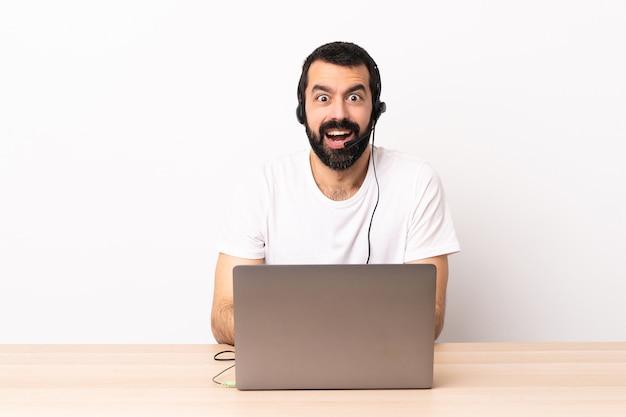 Uomo di telemarketing che lavora con un auricolare e con il laptop con espressione facciale a sorpresa