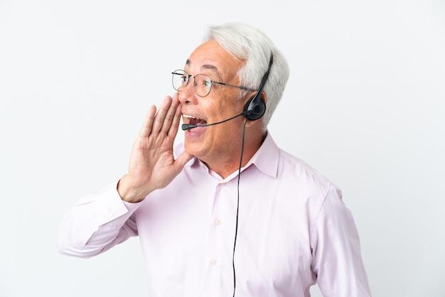 Telemarketer uomo di mezza età che lavora con un auricolare isolato su sfondo bianco che grida con la bocca spalancata di lato