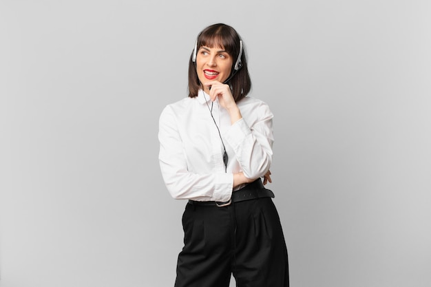 Donna del telemarketing che sorride con un'espressione felice e sicura con la mano sul mento, chiedendosi e guardando di lato