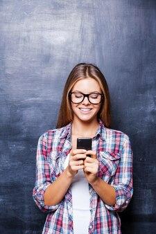Presepe telefonico. giovani donne allegre che tengono il telefono e sorridono mentre stanno in piedi contro la lavagna