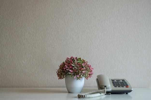 Telefono e vaso di fiori sulla scrivania sullo sfondo del muro grigio