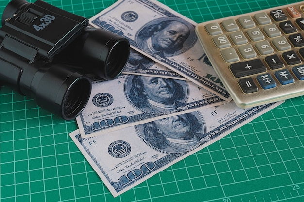 Telescopio o binoculare e denaro delle banconote in dollari usa sul tavolo. concetto di visione aziendale.