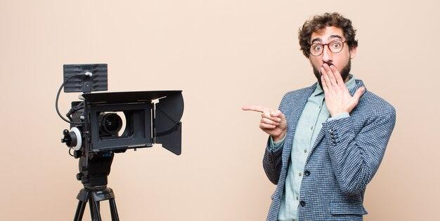 Presentatore televisivo felice, scioccato e sorpreso, coprendosi la bocca con la mano e indicando lo spazio laterale della copia