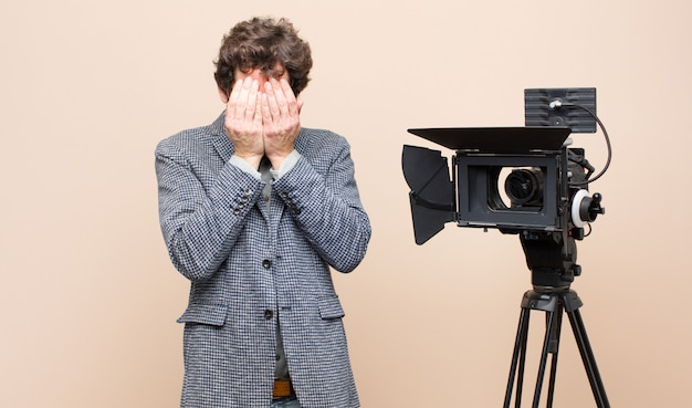 Presentatore televisivo triste, frustrato, nervoso e depresso, che copre il viso con entrambe le mani, piange