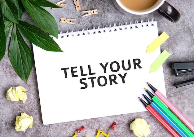 Racconta la tua storia su un quaderno con una tazza di caffè, fogli compressi, pastelli e pinzatrice