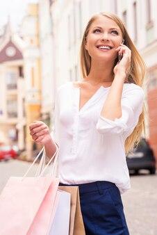 Dire all'amico delle vendite. bella giovane donna sorridente che tiene le borse della spesa e parla al telefono cellulare mentre sta in piedi all'aperto