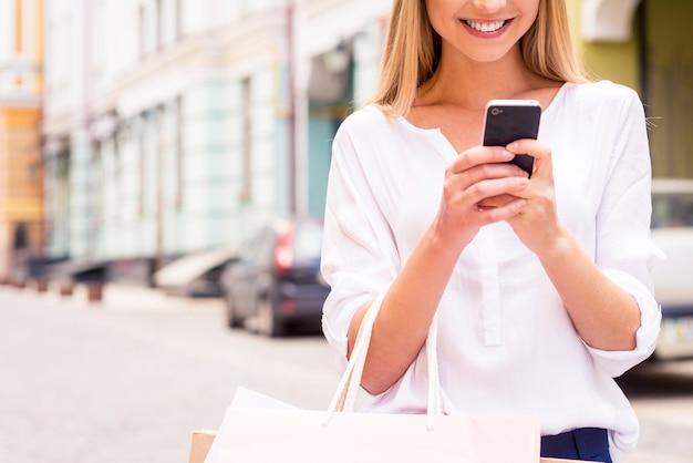 Dire all'amico delle vendite. primo piano di bella giovane donna sorridente che tiene le borse della spesa e il telefono cellulare mentre sta in piedi all'aperto