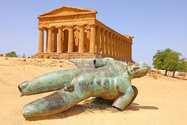 Tempio della concordia e la statua di icaro caduto, nella valle dei templi, agrigento, sicilia, italia