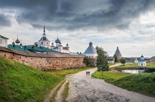 Templi e torri del monastero di solovetsky e la strada tra le colline sotto una nuvola scura sulle isole solovetsky