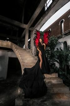 Concetto di tentatrice. la donna sul viso appassionato gioca un gioco di ruolo. demone sexy ragazza in abito nero con ali rosse, diavolo pieno di desiderio in piedi sulle scale