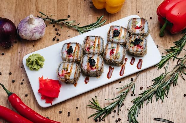 Tempura maki sushi deep fried sushi roll fatta di gamberetti avocado e crema di formaggio all'interno sushi roll servito su piastra bianca sushi giapponese cibo