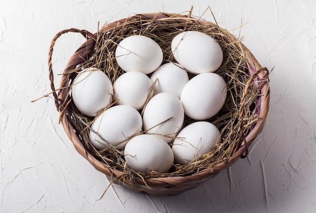 Dieci uova di gallina bianca in un cesto con fieno su uno sfondo bianco.