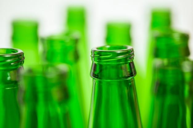 Dieci bottiglie verdi. una bottiglia in primo piano a fuoco