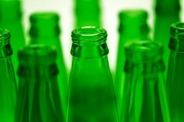 Dieci bottiglie di birra vuote verdi sparate. una bottiglia centrale a fuoco.