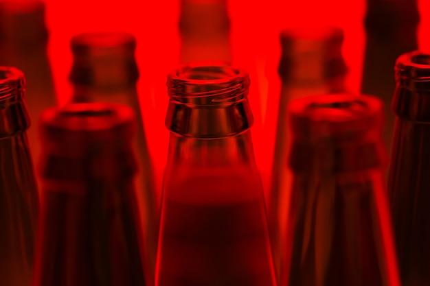 Dieci bottiglie di birra vuote verdi sparate con luce rossa. una bottiglia centrale a fuoco.