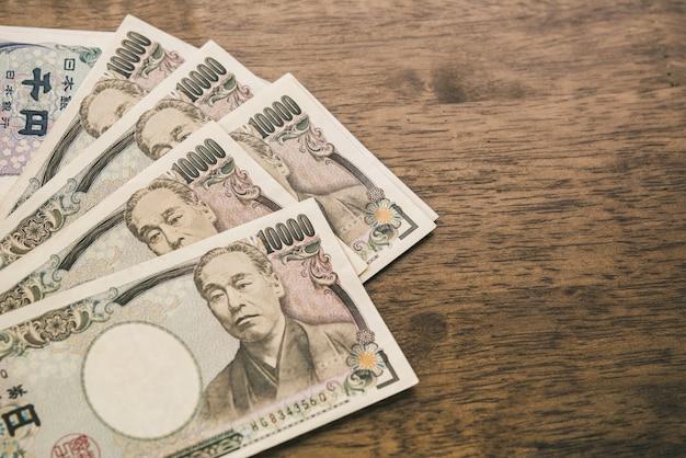 Diecimila banconote giapponesi di yen sulla tavola di legno