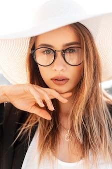 Tenera bella giovane donna con labbra piuttosto sexy con occhi incredibili in gioventù alla moda in cappello alla moda in blazer nero gode di luce solare intensa all'aperto. ritratto affascinante ragazza sulla strada in una giornata di sole.