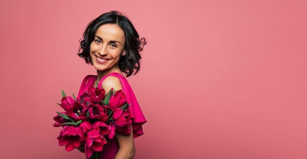 Tenero bouquet. foto ravvicinata di una donna bruna vestita di rosa, che tiene in mano un mazzo di tulipani e sorride felice.