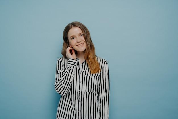 Tenera ragazza adolescente europea carina che indossa una camicia bianca con strisce nere, esprimendo la sua timidezza con la testa inclinata e i capelli dietro l'orecchio, in posa in studio davanti a sfondo azzurro