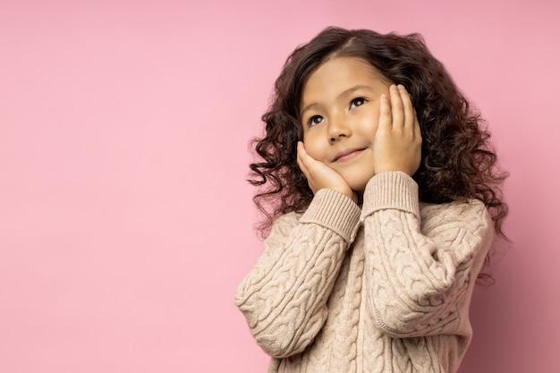 Tenera ragazzina sognante con i capelli scuri ricci, tenendo i palmi sulle guance, avendo un'espressione pensierosa, sognando, indossando un maglione beige, in posa sul muro rosa con spazio vuoto.