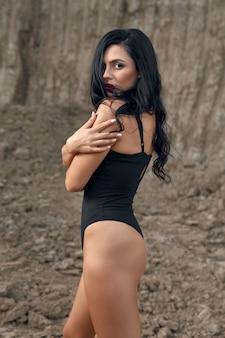 Modello femminile tenero con trucco e acconciatura vestito in tuta nera in piedi sexy nella cava di sabbia.