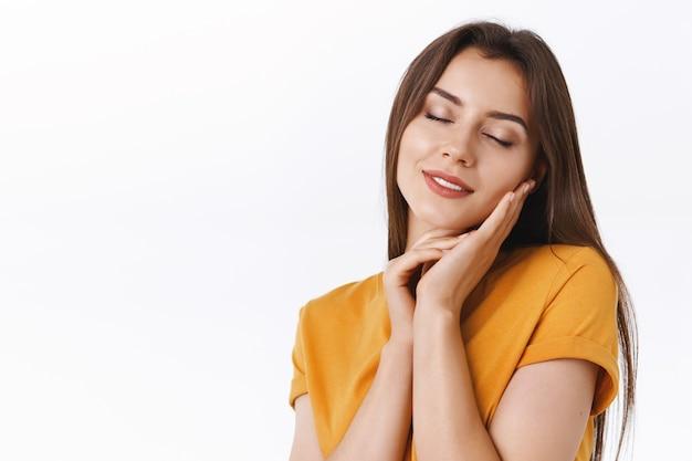 Tenera, femminile e sognante giovane donna attraente romantica in t-shirt gialla, che tocca delicatamente la pelle morbida senza macchie, chiude gli occhi e sorride con un'espressione seria, sognando qualcosa di adorabile