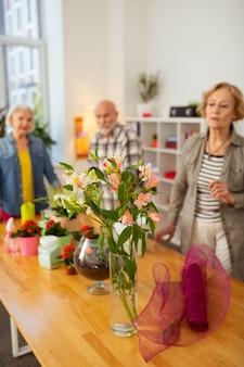 Fiori teneri. messa a fuoco selettiva dei fiori in piedi nel vaso con le persone che li guardano