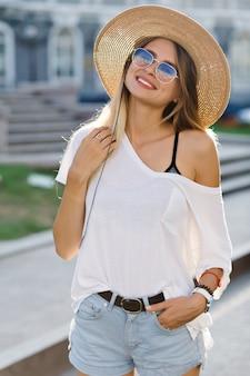 Una tenera ragazza con trucco nudo, denti bianchi vestita camicia bianca con spalle nude e pantaloncini di jeans, cappello e occhiali da sole posa con un sorriso adorabile alla luce del sole, in città