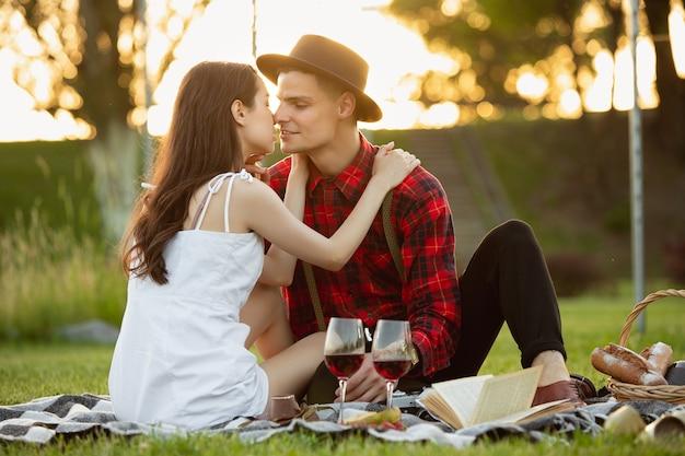 Momenti teneri. giovani coppie caucasiche che si godono il fine settimana insieme nel parco il giorno d'estate. sembri adorabile, felice, allegro. concetto di amore, relazione, benessere, stile di vita. emozioni sincere.