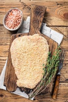 Cotoletta alla milanese impanata cruda tenera su una tavola di legno con timo. fondo in legno. vista dall'alto.