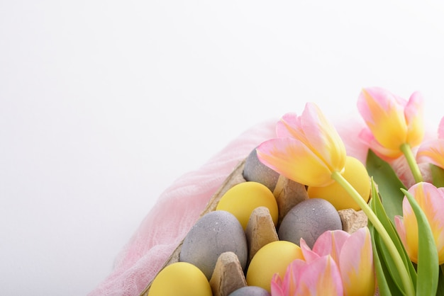 Tenera primavera pasqua composizione di uova pasquali tulipani rosa su sfondo bianco con copia spazio