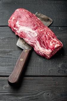 Filetto o filetto di manzo tagliato crudo marmorizzato set di carne, con il vecchio coltello da macellaio, su sfondo tavolo in legno nero