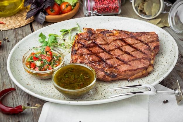Bistecca di filetto sulla piastra con salsa, su un tavolo di legno