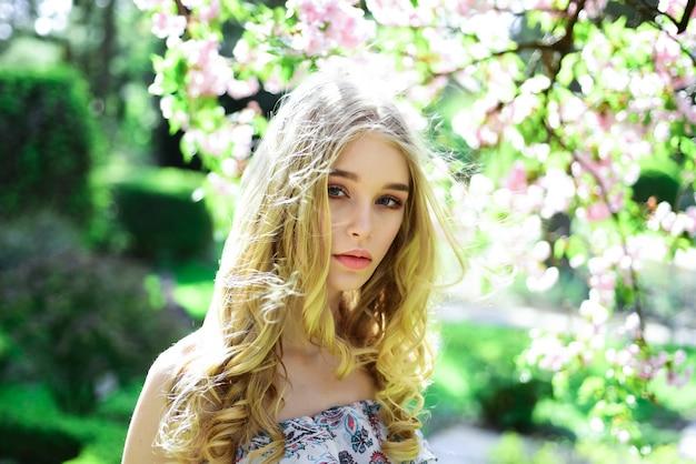 Ragazza di concetto di tenerezza sulla bionda tenera viso sognante guarda alla natura della fotocamera defocused giovane donna godersi la natura in giardino sulla soleggiata giornata di primavera