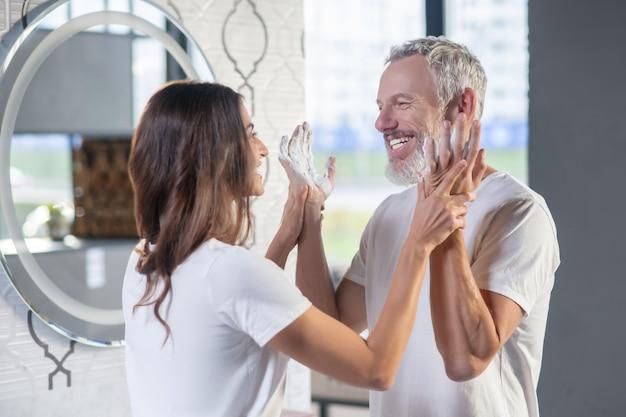 Tenerezza, sensazione. sorridente donna dai capelli scuri che tengono le mani del marito felice dai capelli grigi in schiuma di sapone