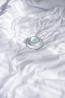 Tenerezza. bianco con tazza bordata di nero e piattino su biancheria da letto stropicciata bianca come la neve alla luce del giorno al chiuso