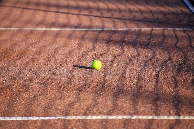 Palla da tennis su un campo in terra battuta. sfondo sportivo